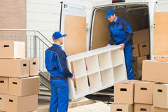Movers Unloading Furniture From Truck. Young male movers unloading furniture and cardboard boxes from truck on street Royalty Free Stock Images