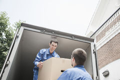 Movers unloading a moving van, passing a cardboard box Stock Images