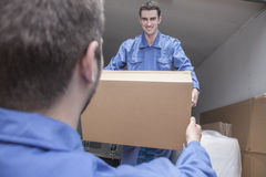 Movers unloading a moving van, passing a cardboard box royalty free stock photo