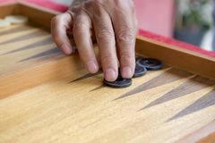 Moves in a backgammon game. A man moves a pool in a backgammon game royalty free stock images