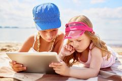 Movie on the beach. Two confused little girls with touchpad lying on sandy beach on hot day and watching online movie Stock Images