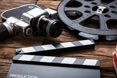 Movie Camera With Film Reel And Clapper Board On Wood royalty free stock photo