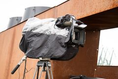 Movie camera mounted on a tripod in a rain cover. Stock Image