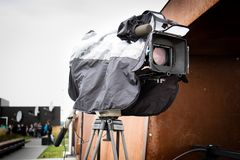 Movie camera mounted on a tripod in a rain cover. royalty free stock images