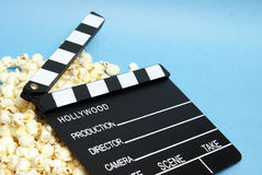 Movie Clapboard. A movie clapboard rests on a pile of fresh popcorn Royalty Free Stock Photo
