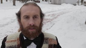 Movie clapper, bearded man in a suit and bow tie on a background of winter stock video footage
