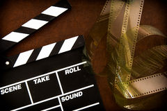 Movie clapper board detail and unrolled  filmstrip Stock Photography