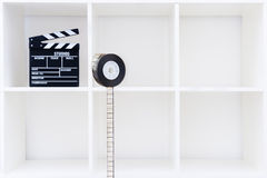 Movie clapper board and film reel on white bookshelf Royalty Free Stock Photos