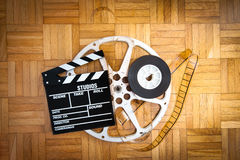 Movie clapper board and film reel on wooden floor Stock Image