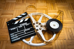 Movie clapper board and film reel on wooden floor Royalty Free Stock Photography