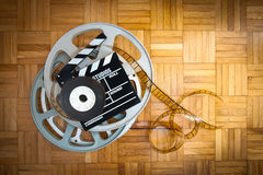 Movie clapper board and film reel on wooden floor Royalty Free Stock Photo