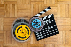 Movie clapper board and film reel on wooden floor. Movie clapper board cinema and super 8 coloured film reels horizontal frame on wooden floor royalty free stock photography