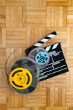 Movie clapper board and film reel on wooden floor. Movie clapper board cinema and super 8 coloured film reels horizontal frame on wooden floor stock image
