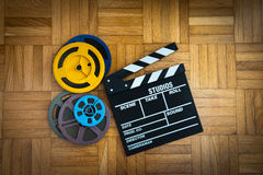 Movie clapper board and film reel on wooden floor. Movie clapper board cinema and super 8 coloured film reels horizontal frame on wooden floor stock images