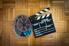Movie clapper board and film reel on wooden floor. Movie clapper board cinema and super 8 coloured film reels horizontal frame on wooden floor stock photography