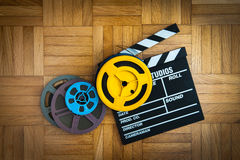 Movie clapper board and film reel on wooden floor. Movie clapper board cinema and super 8 coloured film reels horizontal frame on wooden floor stock photo