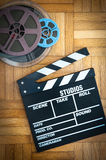 Movie clapper board and film reel on wooden floor. Movie clapper board cinema and super 8 coloured film reels vertical frame on wooden floor royalty free stock images