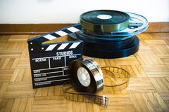 Movie clapper board and film reel on wooden floor. 35 mm cinema movie clapper board and film reels in background on wooden floor royalty free stock photo