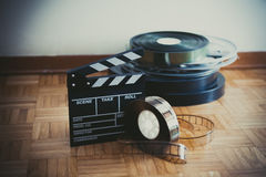 Movie clapper board and film reel on wooden floor. 35 mm cinema movie clapper board and film reels in background on wooden floor pastel colors royalty free stock photography
