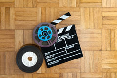 Movie clapper board and film reel on wooden floor. Movie clapper board with super 8 and 35 mm coloured film reels on wooden floor royalty free stock image