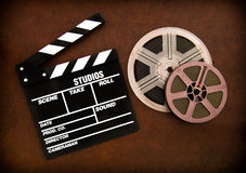 Movie clapper board and film reels detail on wooden floor. Movie clapper board and colored film reels detail on brown table royalty free stock images