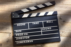 Movie clapper board. Film slate or movie clapper board on wood background Royalty Free Stock Images