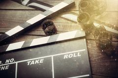 Movie clapper board and film tapes on wooden. Movie clap clapper take action entertainment blue background Royalty Free Stock Image