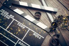 Movie clapper board and film tapes on wooden. Movie clap clapper take action entertainment blue background Stock Photos