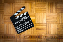 Movie clapper board and filmstrip reel on wooden floor Royalty Free Stock Photo