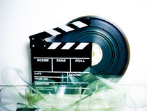Movie clapper board and 35 mm film reel. On white background vintage color effect stock photo
