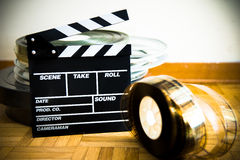 Movie clapper board and 35 mm film reel on wooden floor Royalty Free Stock Images