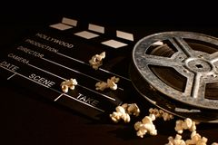 Movie clapper board with popcorn on the wooden table royalty free stock photos