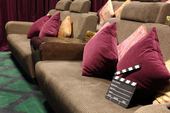 Movie clapper board on soft sofa with cushions Stock Photo