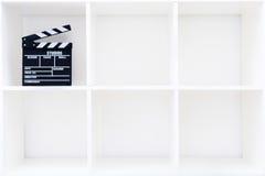 Movie clapper board on white bookshelf Stock Photos