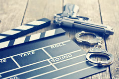 Movie clapper and gun with handcuffs Royalty Free Stock Image