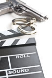 Movie clapper and gun with handcuffs. On white background Stock Photos