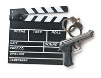 Movie clapper and gun with handcuffs. On white background Royalty Free Stock Photos
