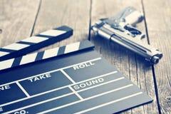 Movie clapper and gun. Vintage photo shot of movie clapper and gun Stock Photography