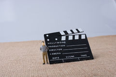 Movie  clapper and a man figurine Stock Photos