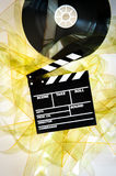 Movie clapper on 35 mm cinema reel unrolled yellow filmstrip. On white background vertical Royalty Free Stock Photo