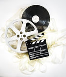 Movie clapper on 35 mm cinema reels with unrolled filmstrip Royalty Free Stock Photography