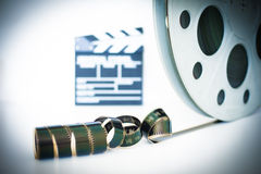 Movie clapper and 35 mm film roll on white Royalty Free Stock Image
