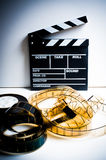 Movie clapper with 35 mm film on white Stock Image
