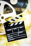 Movie clapper on 35mm yellow unrolled film and cinema reels. On neutral background vertical frame stock image