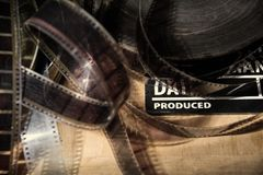 Movie clapper and old film reel on a wooden background stock photos