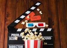 Movie clapper, popcorn, 3d glasses on a wooden Royalty Free Stock Image