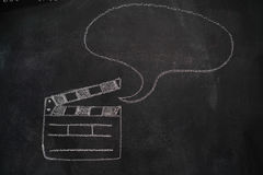 Movie clapper with speech bubble on chalkboard Stock Image