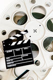 Movie clapper on two 35 mm cinema reels with film vertical Royalty Free Stock Image