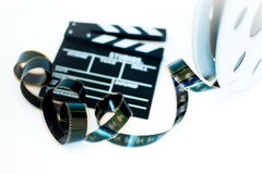 Movie clapper and vintage 35 mm film cinema reel on white Stock Images