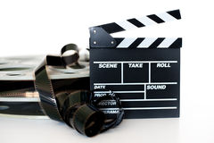 Movie clapper and vintage 35 mm film cinema reel on white. Background filmstrip unrolled selective focus Stock Photography